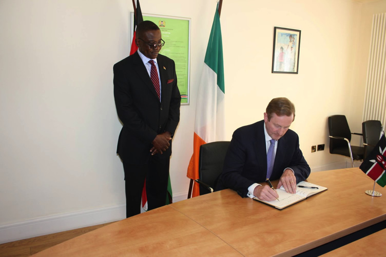 Mr. Enda Kenny Rt. Hon. Prime Minister of Ireland signing the Book and looking on is Amb. Richard Opembe